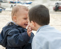 Children playing at beach two small brother boys together a boat in background Royalty Free Stock Photos