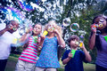 Children playing with bubble wand in the park Royalty Free Stock Photo
