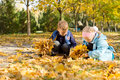 Children playing in a carpet of autumn leaves Royalty Free Stock Photo