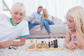 Children playing chess in the living room two Stock Image