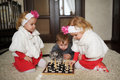 Children playing chess lying on floor