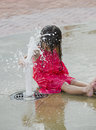 Children playing in a city water park play ground the bubbling up front of her Royalty Free Stock Image