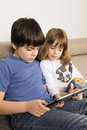 Children playing with a digital tablet on sofa Royalty Free Stock Image