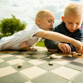 Children playing draughts or checkers board game outdoor little boys clever kids thinking in the park childhood and development Royalty Free Stock Photos
