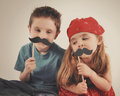 Children playing with fake dressup mustaches two are on an isolated background for a creative or imagination concept Stock Photos
