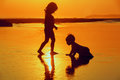 Children playing with fun on the sunset sea beach Royalty Free Stock Photo