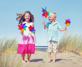 Children Playing Pinwheels by the Coastline Royalty Free Stock Photo