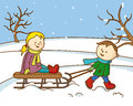 Children playing with a sled in the snow Royalty Free Stock Photo