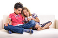 Children playing smartphone two girl and boy using smart phone indoor sofa Royalty Free Stock Images