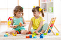 Children playing together with building blocks. Educational toys for preschool and kindergarten kids. Little girls build Royalty Free Stock Photo
