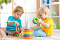 Children playing together. Toddler kid and baby play with blocks. Educational toys for preschool kindergarten child Royalty Free Stock Photo