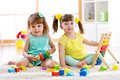Children playing together. Toddler kid and baby play with blocks. Educational toys for preschool and kindergarten child. Little gi