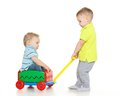 Children are playing with toy car handcart on a white background one little boy sits in handcart another child pulls him merry Royalty Free Stock Photos