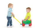 Children are playing with toy car handcart on a white background one little boy sits in handcart another child pulls him merry Stock Photos