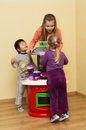 Children playing with toy cooker young girls and boy in room Royalty Free Stock Images