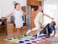 Children playing twister at home two cheerful little girls and teenage boy with Stock Photo