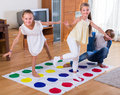 Children playing twister at home two cheerful little sisters and teenage boy Stock Images