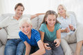 Children playing video games on the couch while parents are watching them behind Stock Image