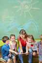 Children in preschool reading book together with a nursery teacher Stock Photos