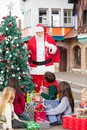 Children with presents looking at santa claus standing by christmas tree in courtyard Stock Photo