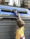 Children pulling a cardboard into recycling container for paper Stock Photos