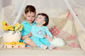 Children and rabbit on a colored blanket in blue suits with white flowers lemons Royalty Free Stock Images