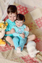Children and rabbit on a colored blanket in blue suits with white flowers lemons Stock Photography