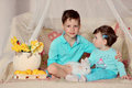 Children and rabbit on a colored blanket in blue suits with white flowers lemons Stock Images