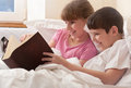 Children read book in bed Stock Image