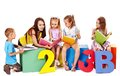 Children reading book sitting at cube Stock Image