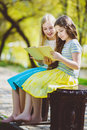 Children reading books at park. Girls sitting against trees and lake outdoor Royalty Free Stock Photo
