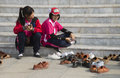 Children removing their shoes before entering building