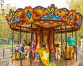 Children ride on the horses on the colorful carousel in the Park Royalty Free Stock Photo