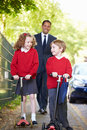 Children riding scooters on their way to school with father looking at each other smiling in background Royalty Free Stock Image