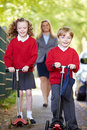Children riding scooters on their way to school with mother in background smiling Royalty Free Stock Image