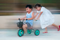 Children riding tricycle young girl pushing with boy on it Royalty Free Stock Images