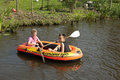Children rowing in a rubber dinghy netherlands group portrait of two boys their boat on the small river the vlist enjoying the Stock Photography