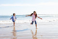 Children running away from breaking waves on beach having fun Stock Photo