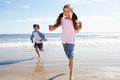 Children running away from breaking waves on beach having fun Stock Images