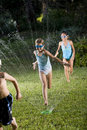 Children running through lawn sprinkler Stock Images