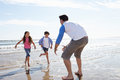 Children running towards father on beach smiling Stock Image