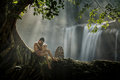 Children in rural sit under a tree on the rocks in a waterfall asia thailand Stock Image