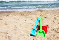 Children s beach toys bucket spade and shovel on sand on a sunny day Royalty Free Stock Images