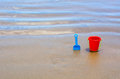 Children s beach toys red bucket and blue spade on sand during sunny day Stock Photos