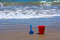 Children s beach toys on seaside red bucket and blue spade on sand with the sea in the background on sunny day Royalty Free Stock Photos