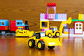 Children`s construction equipment is yellow in the background of a toy building