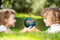 Children s holding world hands against green spring background earth day concept elements image furnished nasa Royalty Free Stock Images