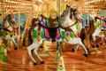 Children`s merry-go-round in an amusement park with colorful horses decorated with glowing light bulbs Royalty Free Stock Photo