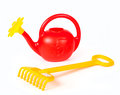 Children`s plastic watering can and yellow rake Royalty Free Stock Photo