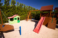 Children s play area well designed with slide trampoline and swing surrounded by trees Stock Images